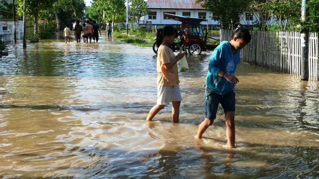 Suguhan Kota Air Gorontalo Tampak Dua Perempuan Berjalan Genangan Banjir